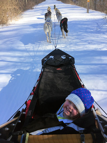 One of the participants at the Maine Winter Cabin Adventure tries her hand at driving the team